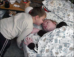 Child leaning over a second child who is lying in a bed