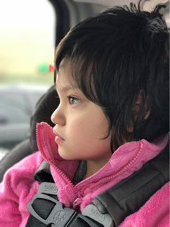 Young girl with Rett syndrome wearing a pink fleece jacket looking out of car window from her carseat