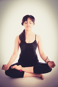 Woman in workout clothes sitting crosslegged with eyes closed and hands on knees