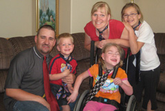 adult male, young boy, girl in wheelchair, adult female behind wheelchair, and pre-teen girl. All family wearing ties.